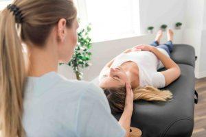 Une Kinésithérapeute effectue une décompression des vertèbres pour diminuer les douleurs cervicales