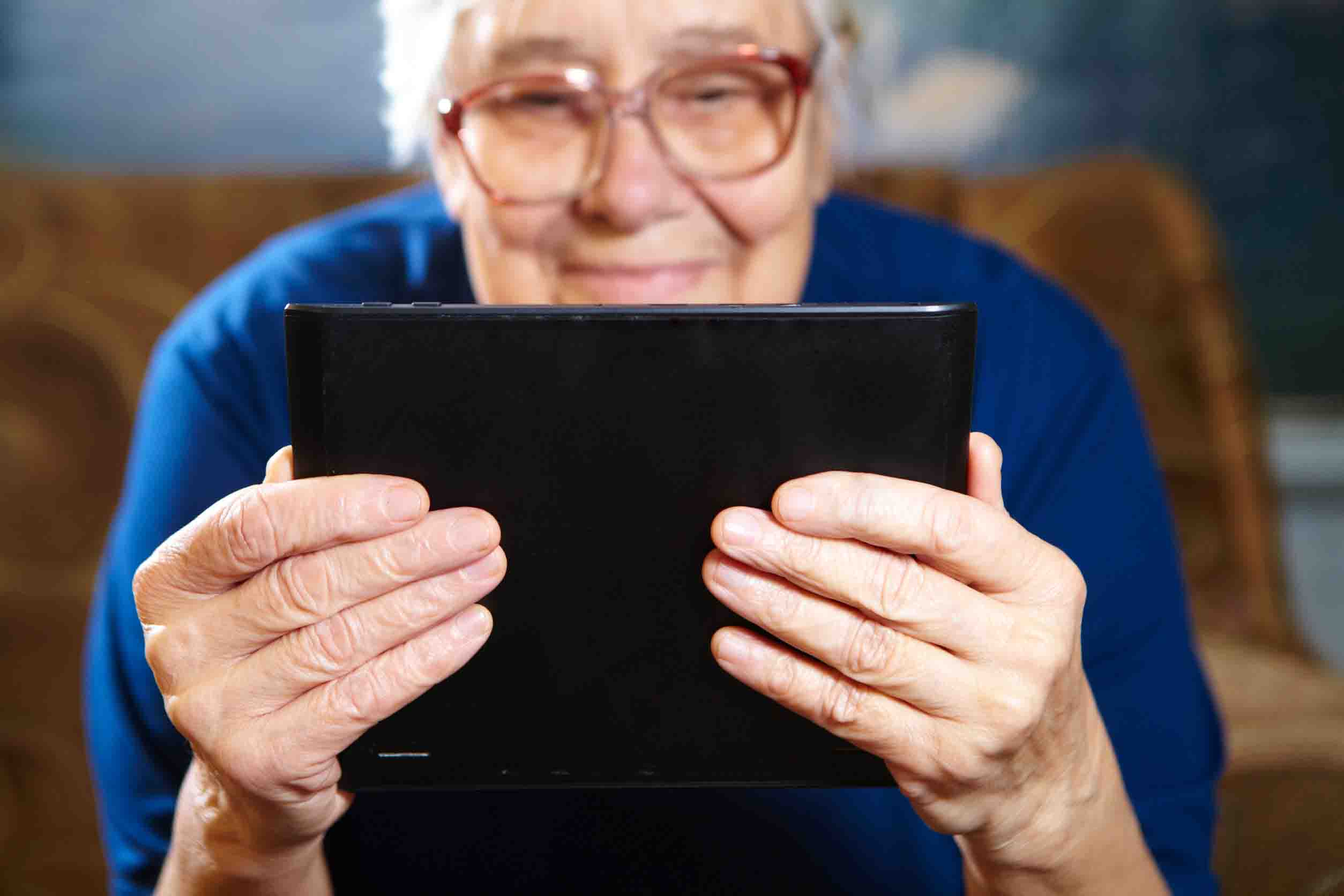 Femme senior qui adopte une bonne position pour regarder sa tablette