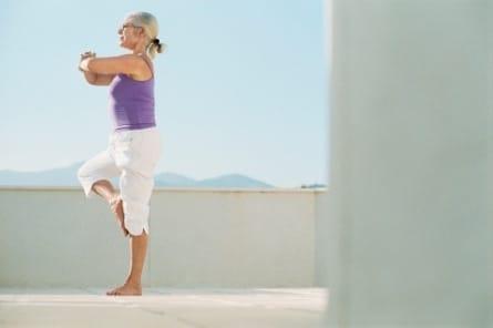 Image montrant une femme senior en équilibre sur une jambe