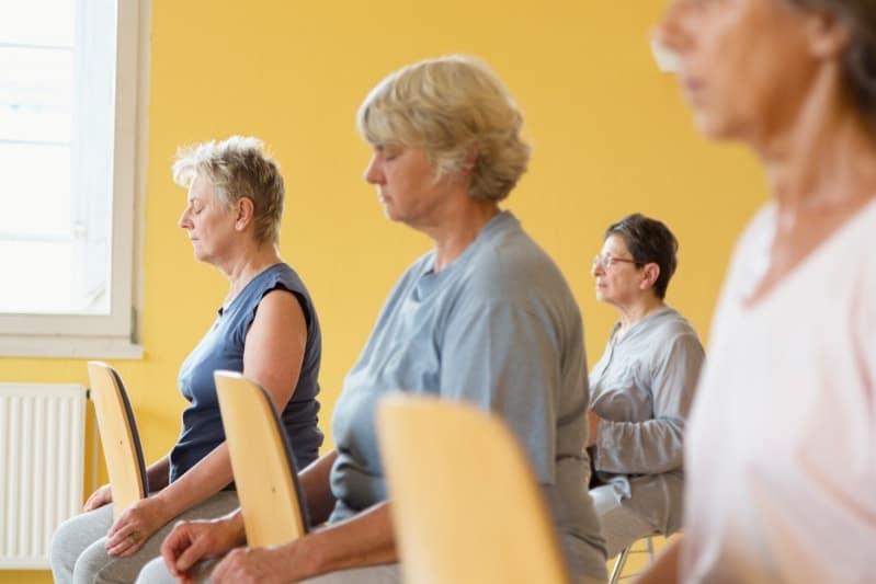 Femme de 60 ans et plus qui pratique du Qi Gong sur chaise