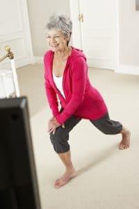 Une femme senior fait des exercices de sport devant sa TV