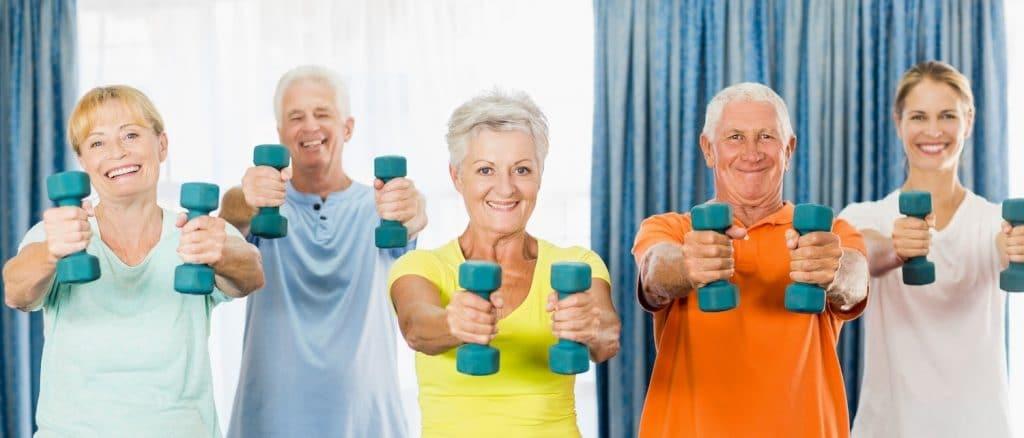 groupe de personnes seniors qui réalisent des exercices de gym douce avec un coach