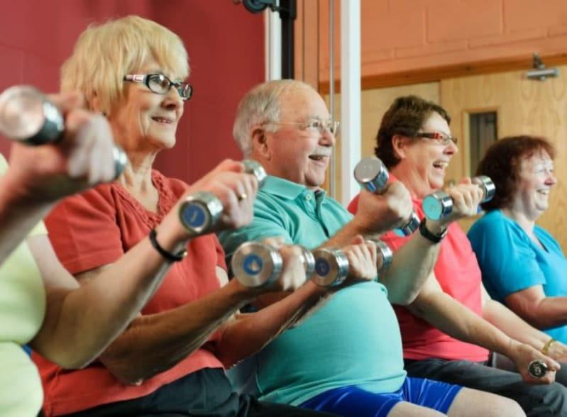 Groupe de seniors qui pratiquent un exercice de gym sur chaise