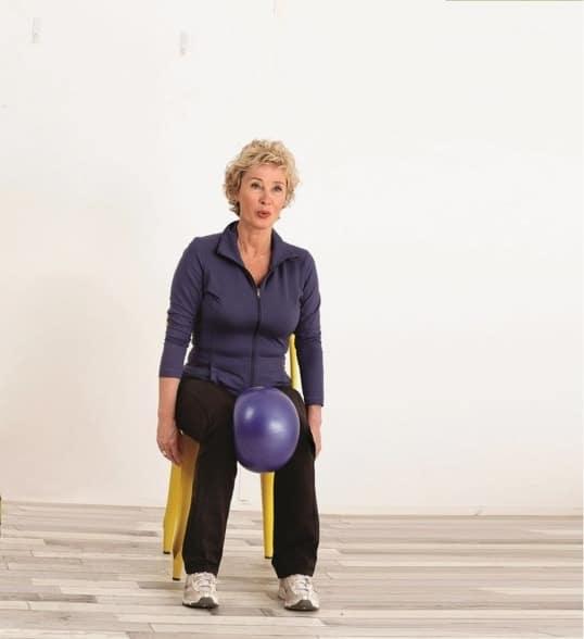 Exercice de gym sur chaise pour senior avec un ballon