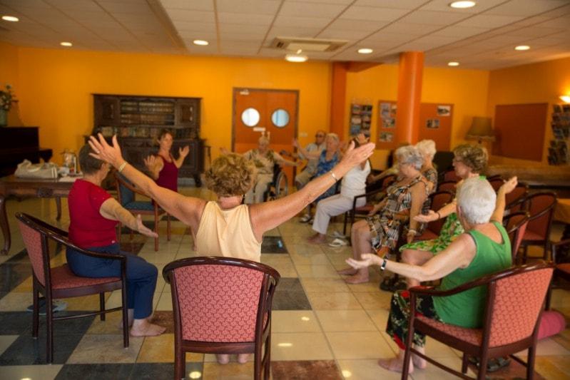 groupe de seniors qui pratique du Qi Gong sur chaise