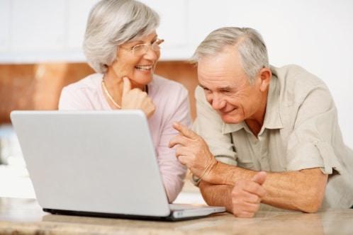Couple de seniors en train de regarder de l'activité physique en vidéo